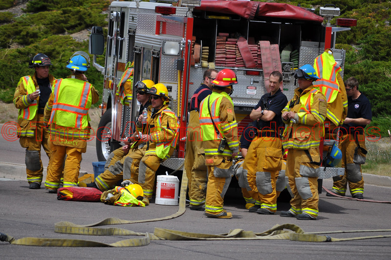 Colorado Springs Fire Fighters on standby as tow truck crews work to get a tractor trailer back on its' wheels after a collision at Fountain Boulevard and Academy Park Loop.
