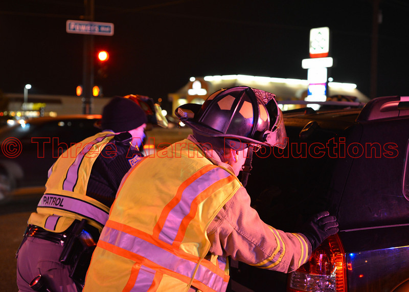 A firefighter and a state patrol officer push a damaged vehicle away from the center of the intersection, at Powers and Palmer Park, to prepare it for towing.