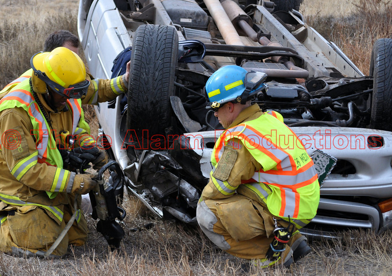 Colorado Springs Engine 8 Firefighters, working to disconnect the battery on a damaged truck involved in an accident on Southbound Powers Boulevard.