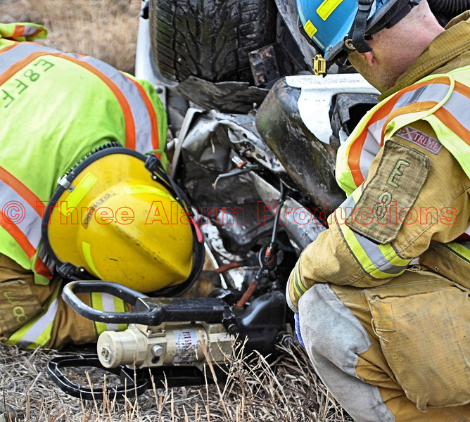 Firefighters working to disconnect the battery on a damaged truck involved in an accident.