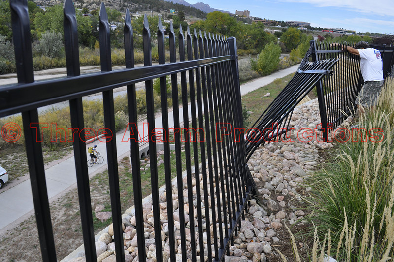 A car goes through this metal fence and drops 50 feet off of this embankment. Driver was taken to the hospital.