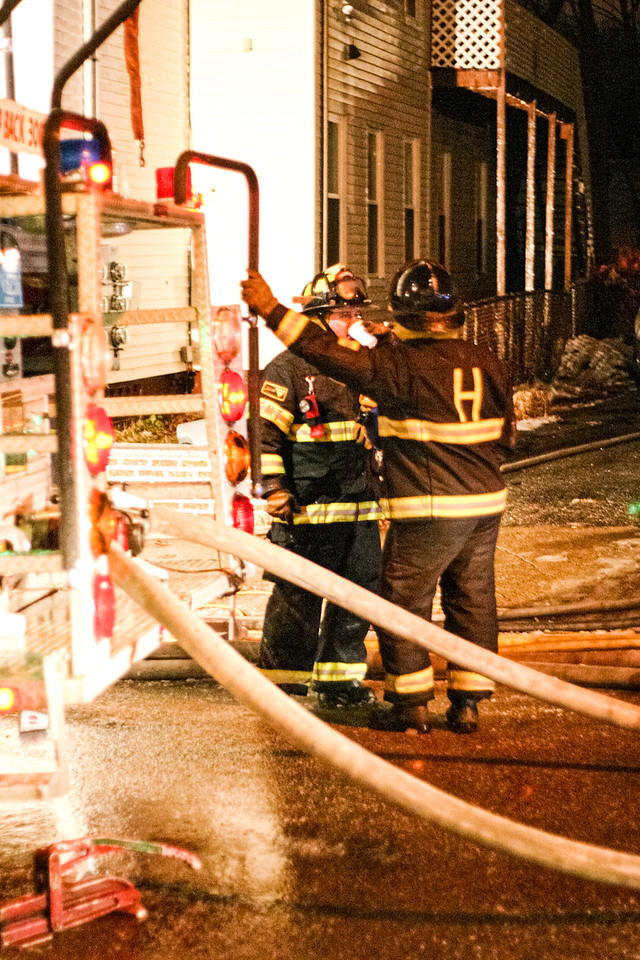 A fire fighter takes a break to sip coffee at a two-alarm blaze at 27 5th Ave. in Haverhill, MA.