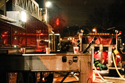 Steaming cups of coffee are abandoned on a fire engine support leg at a two-alarm blaze at 27 5th Ave. in Haverhill, MA.
