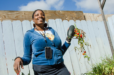 Hobby farmer Keyetta Williams shows homegrown tomatoes from her backyard garden in West Oakland