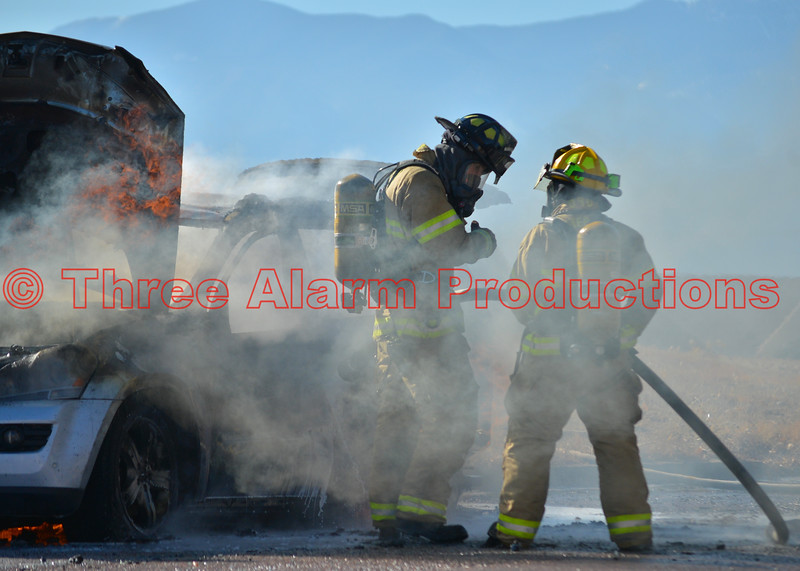 Firefighters working on fire attack of a fully involved vehicle fire in Falcon, Colorado, USA. November 23, 2016