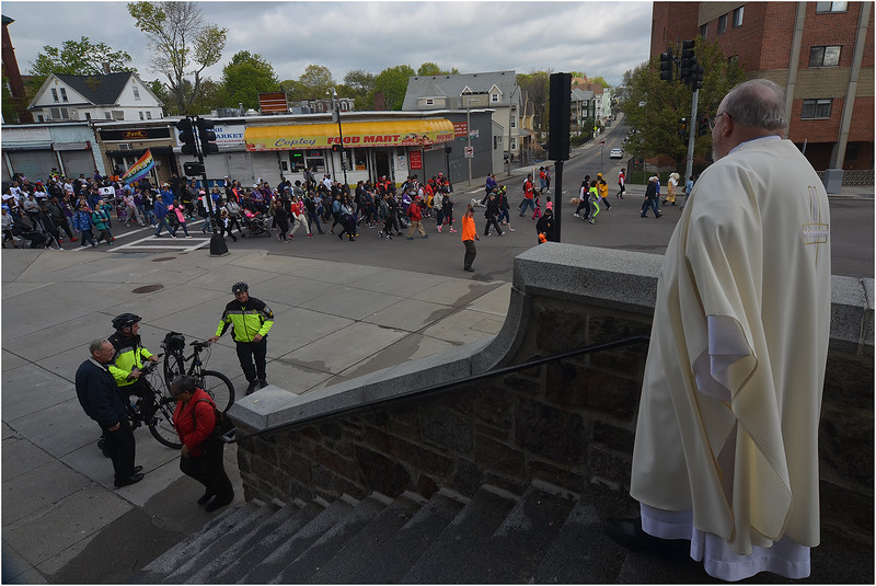 Father Jack Ahern, Pastor of the Dorchester Tri-Parishes, watches the peace walk along Bowdoin Street from the entrance of St. Peter's Church.
