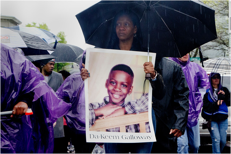 """Charmise Galloway walks along Geneva Avenue with a photo of her son, Da-Keem Galloway. """"My son was murdered over a Boston Celtics hat at age fourteen, in 2004,"""" she said."""