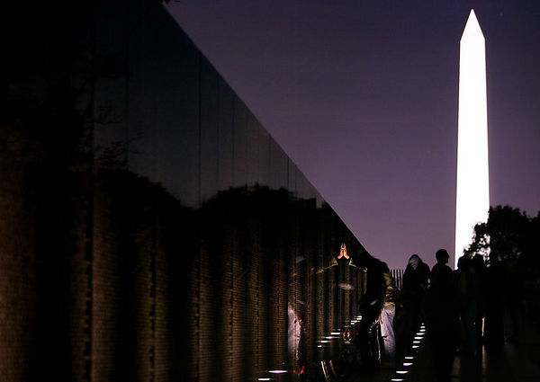 Washington, D.C. 11/11/05 United States National Monuments - Veterans Day - A visitor to the Vietnam War Memorial places a hand on the wall engraved with the names of the thousands of Americans who died during the war. In the background looms the floodlight-lit Washington Memorial. For Travel story by Erika Lovely about how Washington, D.C. is a great place to tour at night because the spectacular monuments can be seen in a new light...flood lights. Photos by Dina Rudick/Globe Staff. Story slugged 13dc