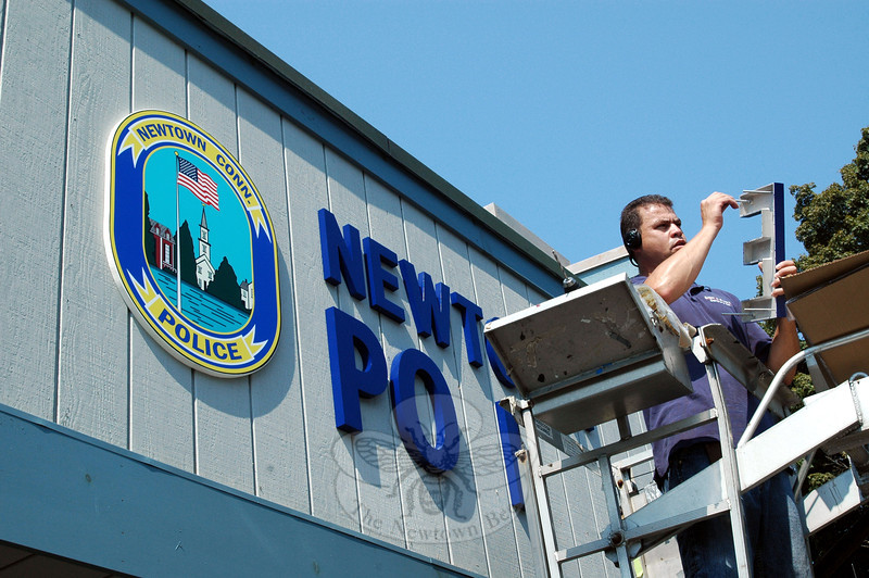 """Jamir Costa, who works for Sign-A-Rama of Danbury, makes some adjustments to a large metal copy of the letter """"E,"""" which is part of the word """"POLICE"""" in a new sign that was installed above the main entrance of the police station on Wednesday, August 21. (Gorosko photo)"""