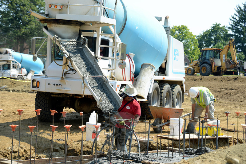 Wet concrete slips down a chute into trenches dug for new ambulance garage footings on Tuesday, August 20. (Bobowick photo)