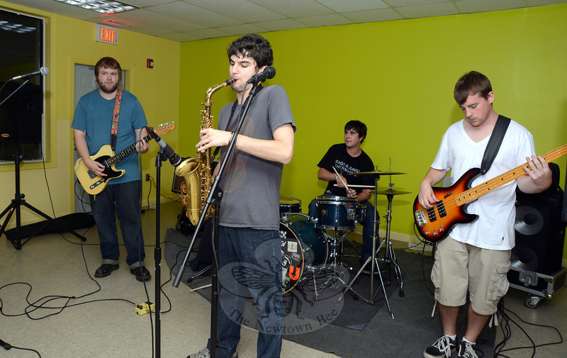 Alto sax player Nico Bonvini, center, plays a show at the Newtown Teen Center on August 16. Bass player Kyle Kearney is to the right in front of drummer Dave Manville. Guitarist, singer, and songwriter Julian Wahlberg is to the left. (Bobowick photo)