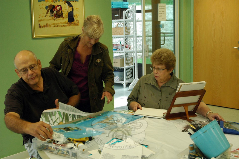 An art class with instructor DeeDee Calvey, center, was held at Newtown Senior Center on Monday, September 9. John Boccuzzi, Sr, left, and Marilyn Como, right, worked on current art pieces while Ms Calvey gave advice about the proper paper to use for sketches for final works, brush techniques, and colors used in artwork, and more. She also praised the accomplishments of her students. (Silber photo)
