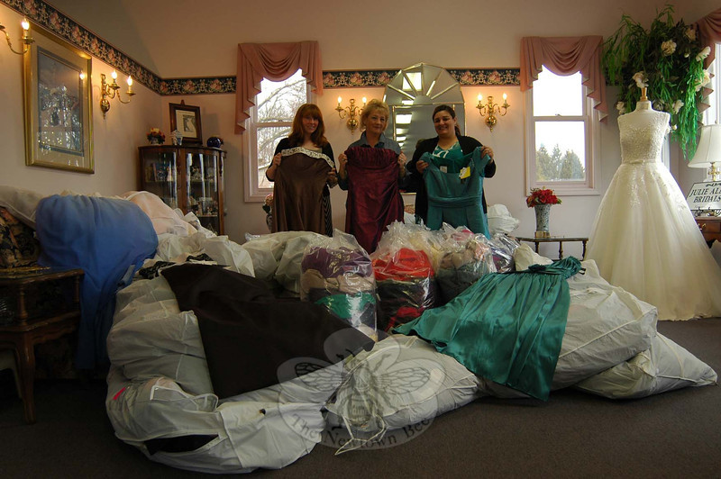 From left, Julie Allen Bridals marketing director and co-manager  Lauren Morehouse, Julie Allen Bridals owner Melanie Mattegat, and Believe in Me Empowerment Corporation case manager Valerie DiNuzzo held three of the 415 dresses the local bridal shop donated to the corporation's Prom Dress/Formal Giveaway slated for April 15 and 17. (Hallabeck photo)