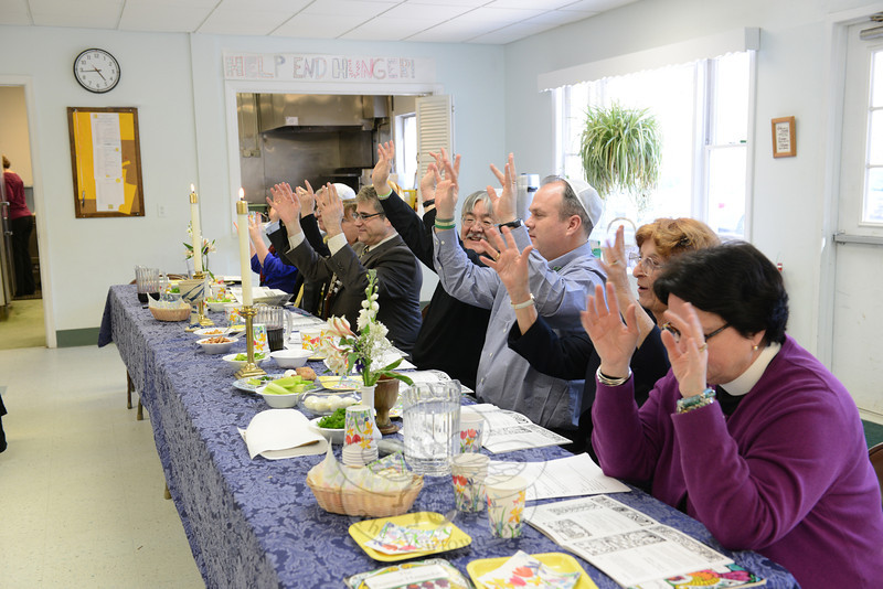 Seated at the head table facing a roomful of guests Sunday afternoon were, from left, Newtown Congregational Church Associate Pastor Alyssa DeWolf, Baha'i Faith of Newtown members John and Margot Woodall, Rabbi Shaul Praver of Congregation Adath Israel, Reverend Mel Kawakami of Newtown United Methodist Church, Senior Pastor Matt Crebbin of Newtown Congregational Church, retired clergy member Janice Touloukian, and Pastor Kathleen Adams-Shepherd of Trinity Episcopal Church. The local clergy leaders led an interfaith Seder at attended by a few dozen people at Newtown United Methodist Church on April 6. (Bobowick photo)