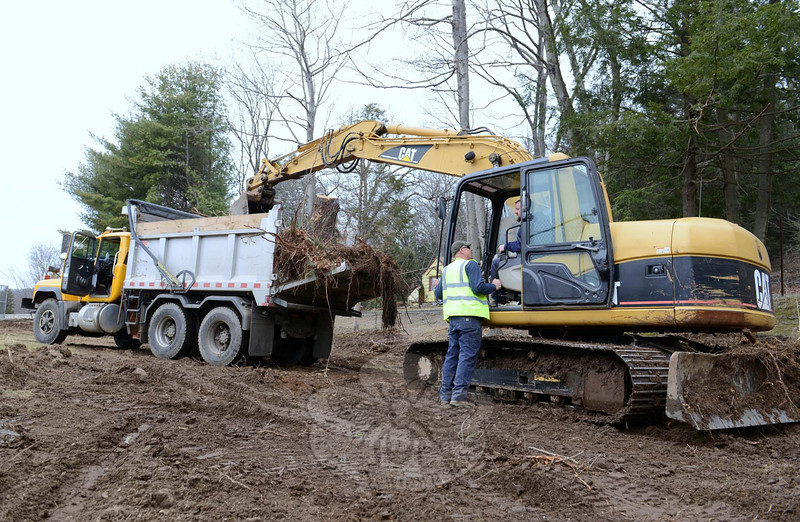 Standing outside the excavator is Bob Fritz, with Jerry Dachenhausen in the machine, as they worked to clear an area at Treadwell Park of tree stumps. Parks & Recreation crew members have been clearing pine, hemlock, and several birch trees, and their stumps, to make way for new tennis courts and a pickle ball court. (Bobowick photo)