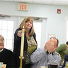 The local clergy leaders led an interfaith Seder at attended by a few dozen people at Newtown United Methodist Church on April 6. Margo Woodall of Baha'i Faith of Newtown lights candles during a Passover ceremony while UMC Reverend Kawakami, left, and Pastor Matt Crebbin of Newtown Congregational Church, with his face covered symbolically, wait for the flame to catch. (Bobowick photo)