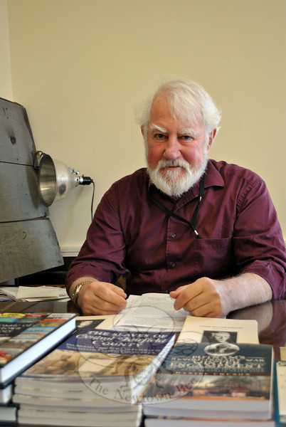 Dan Cruson, longtime member of the board of trustees of the C.H. Booth Library, has resigned from that position. Mr Cruson, town historian, shown in his office at Edmond Town Hall, plans to devote more time to other activities, writing, and research. (Crevier photo)