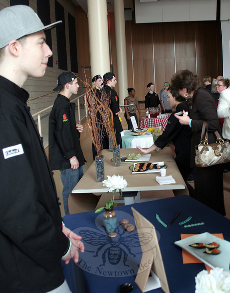 Hayden Savoia (foreground) watches the crowd from his food table. Tables lined three walls of the NHS cafetorium Thursday night, and a few more were set up in the center of the room. Guests were invited to try any of the amuse bouche offerings that appealed to them. (Hicks photo)