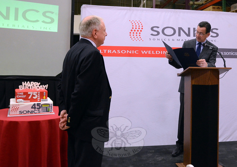 Sonics & Materials founder, President and CEO Robert Soloff, left, receives a proclamation from Governor Dannel P Malloy during a March 20 celebration at the Sonics & Materials Newtown headquarters. Mr Soloff is standing beside a cake marking his 75th birthday, which was also celebrated at the event, which was attended by more than 100 employees, vendors, clients, and dignitaries. (Voket photo)