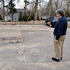 The Reverend Mel Kawakami, of Newtown United Methodist Church, points out one of several sink holes in the church parking lot. An excavation of a section of the lot last year to find out why so many sinkholes occur uncovered a surprise for the minister and many church members — the remains of the historic Fredericka House, collapsed into the foundation. (Crevier photo)