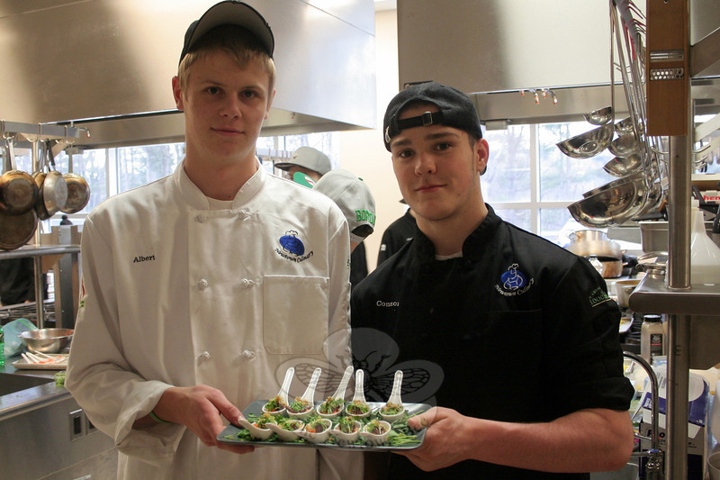 "Albert Dean, left, and Connor LeMay show off a tray of Caramel Miso Braised Beef, their creation for ""A Community Table,"" before guests began arriving Thursday night. (Hicks photo)"