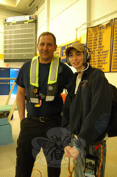 NUSAR President Nick Kopcik, left, showed Newtown High School student Andy DeWolfe how to use a headset to communicate with a NUSAR diver who was in the high school's pool. (Hallabeck photo)