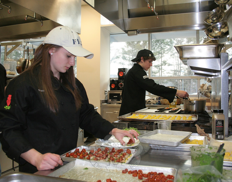 NHS Culinary Arts student Nicole O'Leary plates a set of the appetizers she and her Community Table partner created for the March 27 event: polenta bruschetta with spinach, pesto, and grilled shrimp, topped with a cherry tomato. In the background is Ryan Rosenberger, plating a set of his food offerings. (Hicks photo)