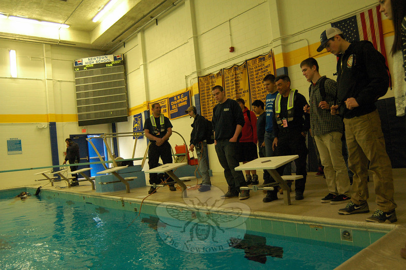 Newtown High School Connections students and members of Newtown Underwater Search and Rescue (NUSAR) stood near the high school's pool on Friday, March 28, during a presentation by NUSAR that included students using headsets to communicate with NUSAR divers underwater. (Hallabeck photo)