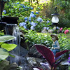 Ms Lincoln gently teases her grandson that the fishing boy statue perched by the waterfall is him. Hydrangea bordering the yard, in the background, came from plants grown by her father, who has passed away. (Crevier photo)
