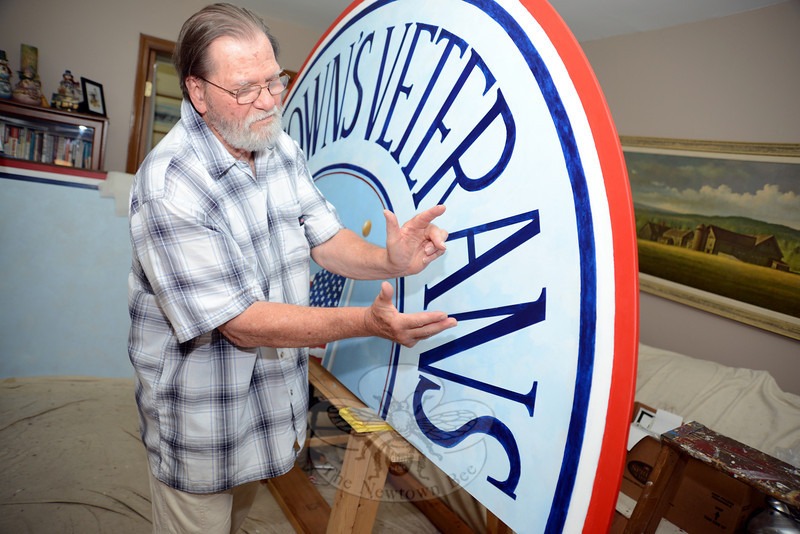 David Merrill talks about the precise measurements and careful work needed to balance the lettering on the mural's top panel. (Bobowick photo)