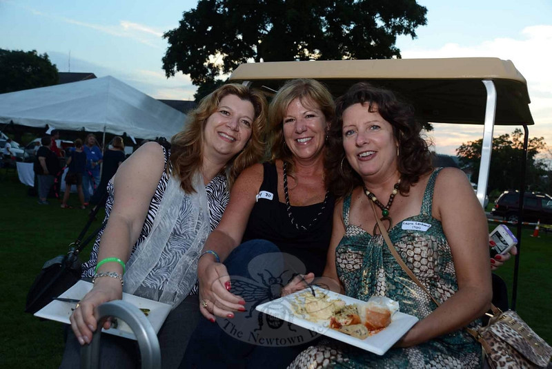 Perched on the back of a golf cart are, from left, Laurie Silber, Amy Edmonds-Casey, and Laura Smolen at The Great Newtown Reunion event held on Saturday, July 27. (Bobowick photo)