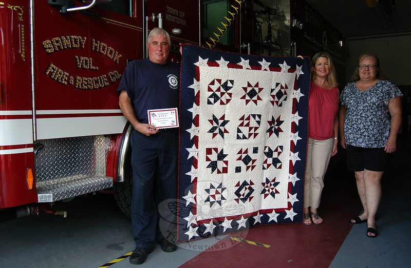 """George Lockwood, Jr, left, accepted a quilt crafted by a group of Washington women, called """"Quilts for Newtown,"""" when it was delivered by former Newtown Junior Women's Club President Christine Grabowski and current Newtown Junior Women's Club President Laura Branchini to Sandy Hook Volunteer Fire & Rescue Co.'s main station on Wednesday, July 24."""
