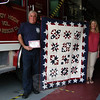 "George Lockwood, Jr, left, accepted a quilt crafted by a group of Washington women, called ""Quilts for Newtown,"" when it was delivered by former Newtown Junior Women's Club President Christine Grabowski and current Newtown Junior Women's Club President Laura Branchini to Sandy Hook Volunteer Fire & Rescue Co.'s main station on Wednesday, July 24."