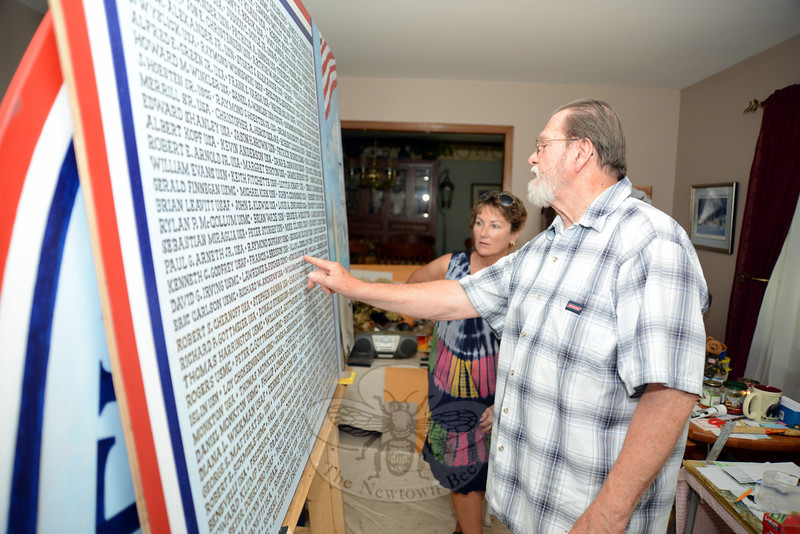 Hundreds of Newtown veterans' names fill the panel of a mural hand painted by Southbury artist David Merrill. With him is Laurie McCollum, a member of the Project Newtown Troops and Veterans committee. (Bobowick photo)