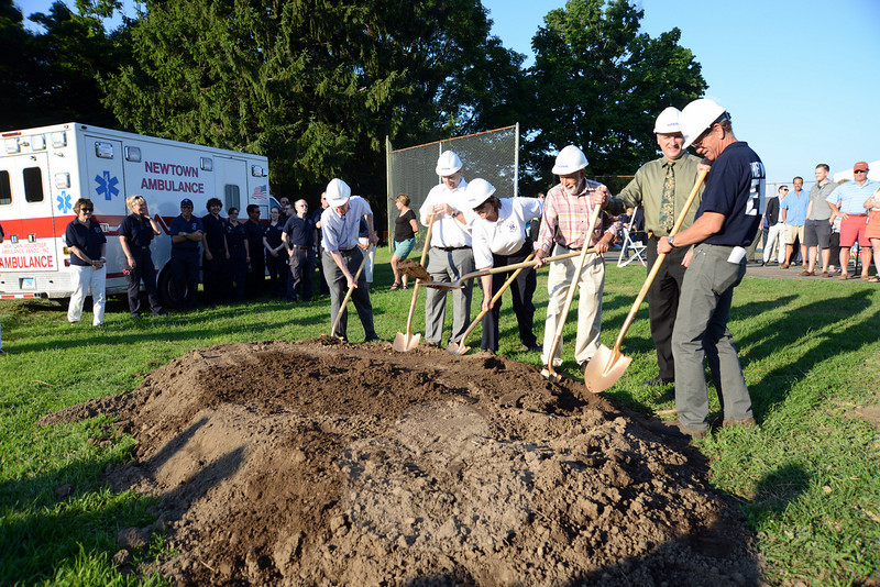 Tossing soil during a ceremonial groundbreaking for a new ambulance garage that will be located in Fairfield Hills are, from left, Newtown Volunteer Ambulance Association (NVAA) Inc Board of Trustees Treasurer Bruce Herring, Joe Nosal of Nosal Builders, ambulance corps Chief Kris Peterson, NVAA Board of Trustees President Bob Grossman, architect Dean Petrucelli, and Building Committee Chairman Stuart Rieve. (Bobowick photo)