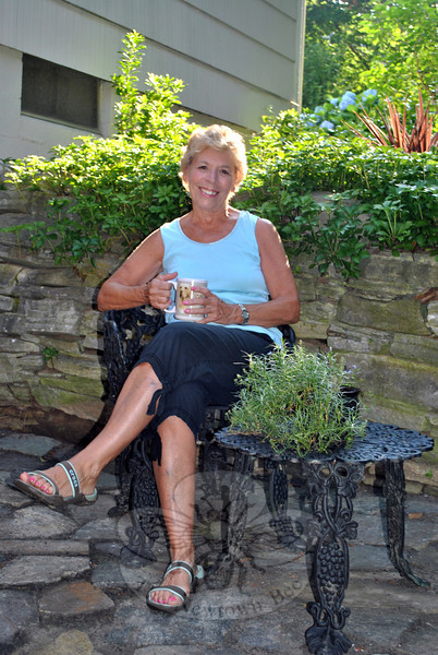 Chris Lincoln enjoys a cup of coffee on her lower level patio, which she built herself. Beyond the stone wall is the garden that surround a waterfall, another of Ms Lincoln's handiworks. (Crevier photo)