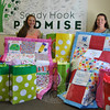 New Fairfield High School sophomore Kaitlyn Gantert, left, holds up the quilt created for Emilie Parker's family, and sponsored by Consolidated Elementary School. Her mother, Tricia Gantert, displays the quilt for Victoria Soto's family, sponsored by Chiropractic Life and Wellness in New Fairfield. Brightly colored bags surround them, filled with 24 more quilts for families who lost a loved one on 12/14.  (Crevier photo)
