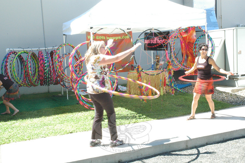 A woman, left, works to get the hang of using a hula hoop at the Newtown Yoga Festival on August 24. (Gorosko photo)