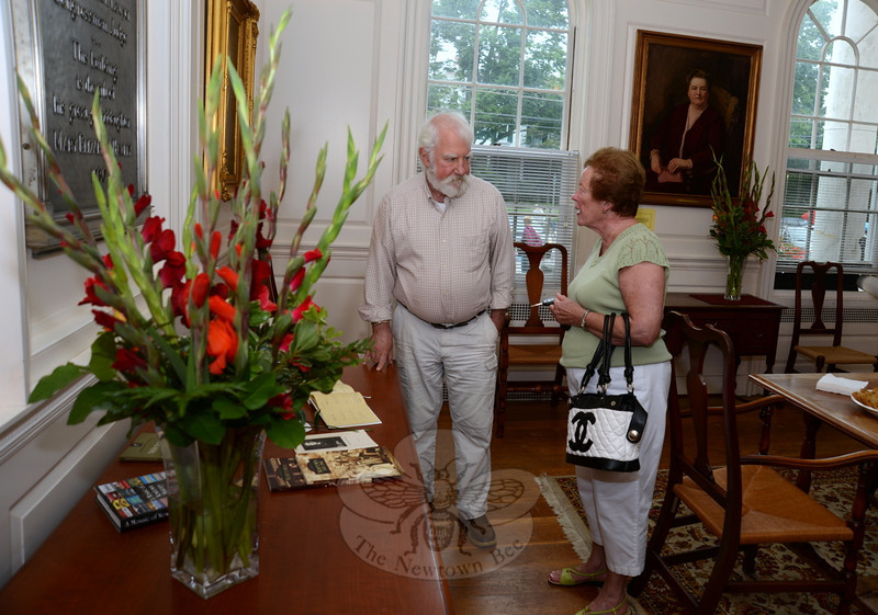 Town Historian Dan Cruson and Marie Sturdevant read through materials set out on a table in the Edmond Town Hall's Mary Hawley Room off the main lobby. Decorating tables are her favorite flowers, gladiolas, set out for her birthday last Thursday, August 22.   (Bobowick photo)