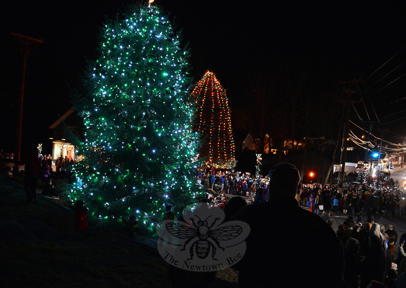 Guests are cast in silhouette by the light of both trees lit in Sandy Hook. The far tree on The Glen property is slated to come down in the future, while the left-hand tree was planted this year. (Bobowick photo)