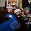 Huddled on the curb, during the Hawleyville tree lighting, with hot cocoa are, from left, Izzy Satmary, Sophie Satmary, and Shanna Adam. (Bobowick photo)