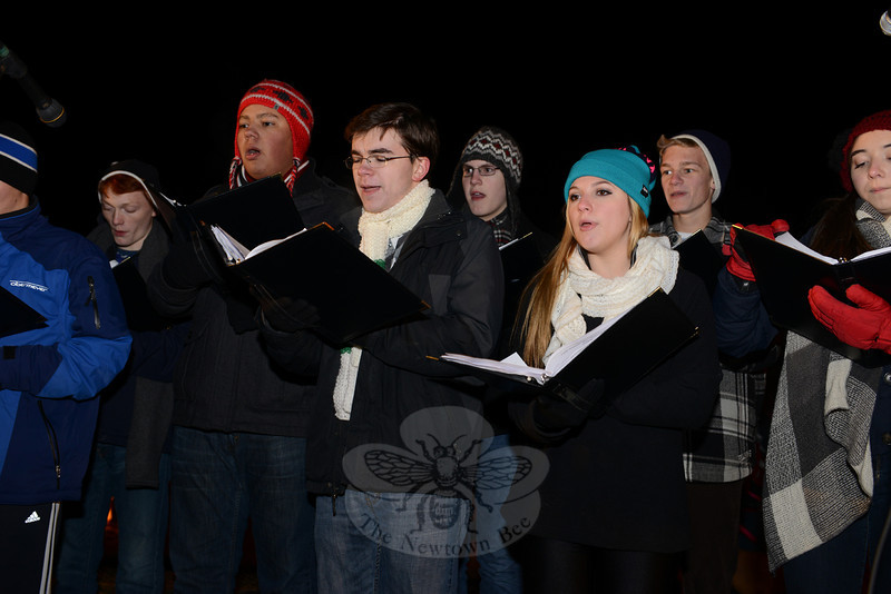 The Newtown High School Singers entertain the crowd with traditional holiday songs minutes before the trees lit and brightened Ram Pasture. (Bobowick photo)