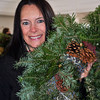"Those in the know wisely filled the narthex of Newtown Meeting House on Main Street 20 minutes before members of The Garden Club of Newtown opened its doors for the Annual Christmas Greens Sale, at 9 am, Saturday, December 7. Within 15 minutes of being welcomed into the building, more than half of the 75 hand-decorated wreaths had been claimed by shoppers. ""I come every year,"" said Kelly Urso, below, showing off the wreath she had selected, ""and I try to get here right at 9 am."" The display of holiday decorations, crafted by the Garden Club members from mostly local and natural materials, included grapevine trees adorned with twinkling lights, tabletop boxwood trees, handmade bows, sprays of white pine and juniper, birch suet bird feeders, and centerpieces of greens tucked into baskets of all shapes and sizes. Hand painted ornaments and elaborately frosted cookies made by Joyce DeWolfe attracted the attention of many browsing the selections, as did the softball-sized ornaments covered in acorn caps and dangling from raffia ribbons. A wreath and a holly tree were the first treas-ures Barbara Myers found, making her way up and down the crowded aisles. Julie Amoony visited the sale for the first time, and was amazed by the selection and reasonable prices. ""I couldn't believe it. It's beautiful!"" exclaimed Ms Amoony, a common observation of dozens of the shoppers present. (Crevier photo)"