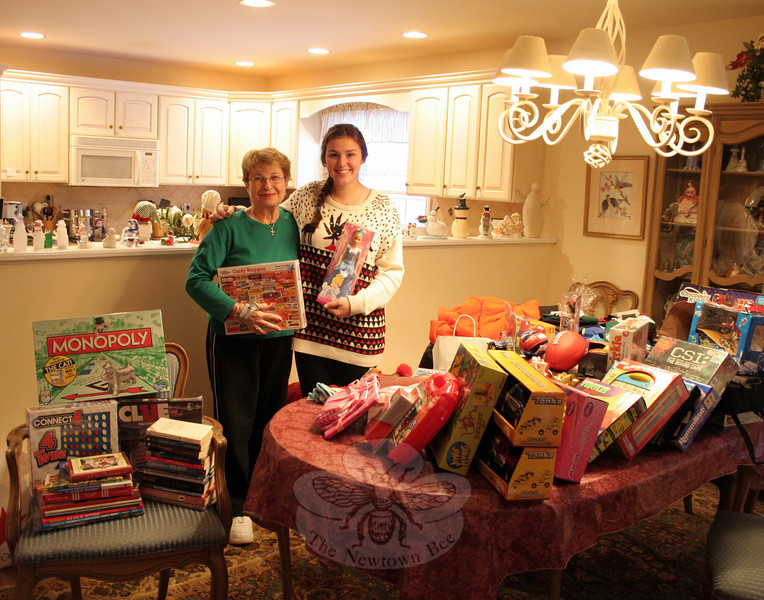 """The Newtown Fund is preparing for Delivery Day, the culmination of its annual Holiday Basket Program during which families in need are provided gifts and other items that will make their lives brighter. Since 2008, Sandy Hook resident Rosemary Trudell, left, with granddaughter Haley, has organized a collection of toys and children's clothing among the residents of Walnut Tree Village II. Her granddaughters have always helped with collecting and organizing the items for her, but older grand-daughter Julia is at college this year and unable to help for the first time. The dining room table of the condo where Leslie and George Trudell live was filled to overflowing on Wednesday, December 11. Many of the Trudells's neighbors were able to donate plenty of toys, books, games, and even clothing again this year. """"The Newtown Fund asked for lots of presents for teenagers this year,"""" said Mrs Tru-dell. """"I think they'll be very happy with what we will be sending over."""" Delivery Day is Saturday, De-cember 14, at Fraser-Woods School. Residents who would still like to participate with donations of gifts and household items to help others get through the holiday season are urged to contact Layne Lescault at 203-270-6481 as soon as possible. (Hicks photo)"""