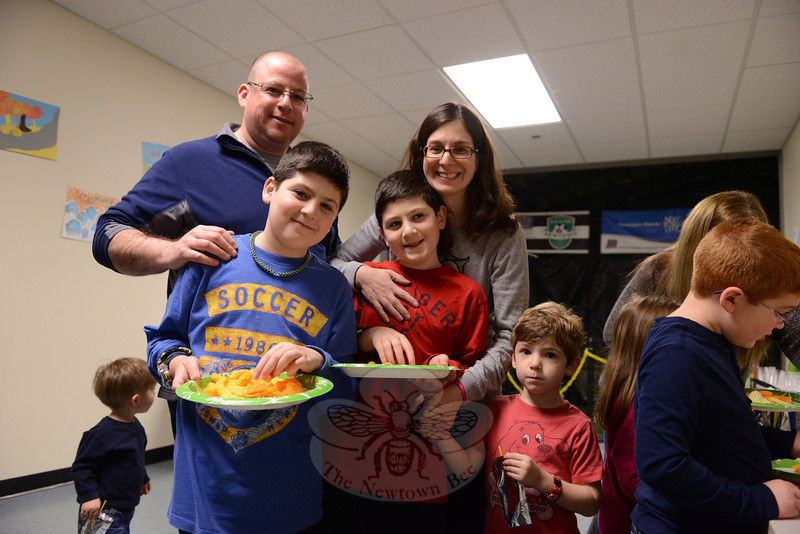 One of the participating families enjoys a snack as the Kids Share Newtown workshop participant re-unite since they had last been together in April. Parents Andrew and Shari Paley stand with, from left, sons Ben, Ethan, and Jacob. (Bobowick photo)