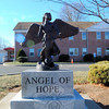 "Monsignor Robert Weiss decided to place an Angel of Hope statue in front of St Rose School as ""a sign of protection for the children entering the building for school and religious education."" Lisa Brown, who coordinated the gift, likes that the angel seems to be watching over everyone on the school property. (Silber photo)"