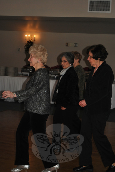 Sherry Milek, left, leads dancers through line dance steps at the Holiday Party. Ms Milek teaches dance at the Newtown Senior Center. (Crevier photo)