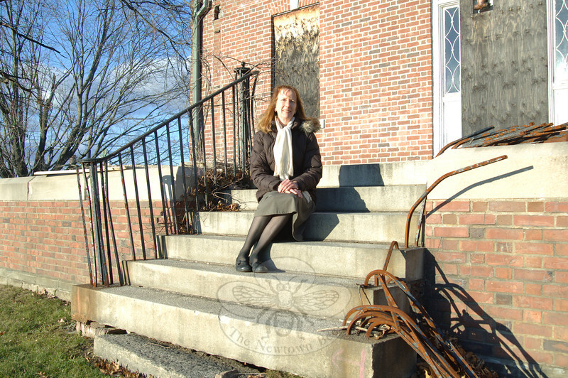Researcher Andrea Zimmermann sits on the steps outside Danbury Hall's crumbling façade. The Newtown resident recently submitted a report to the town detailing the history of Fairfield Hills and Danbury Hall and a cluster of single-family homes specifically. (Bobowick photo)