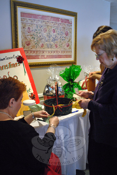 Senior Center member Mary Ann Posser, seated, sells raffle tickets at the Annual Senior Center Holiday Party. Ticket purchasers had the chance to win gift baskets, a 50/50 raffle, or a hand knit afghan blanket.	(Crevier photo)