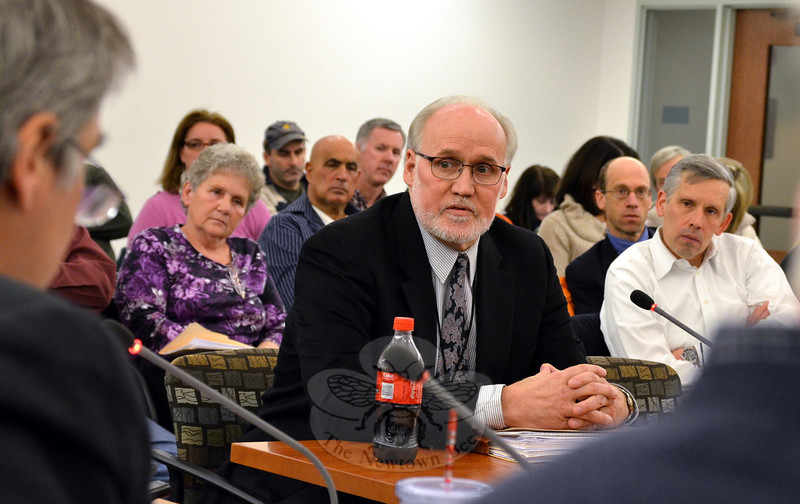 Newtown Land Use Director George Benson listens to a question during a December 18 Legislative Council meeting during which officials discussed the option of taking the residential property at 12 Riverside Road to develop a new entrance driveway to Sandy Hook School. Property owner Susan Oberstadt is seated, listening, just behind and to the left of the land use official. (Voket photo)